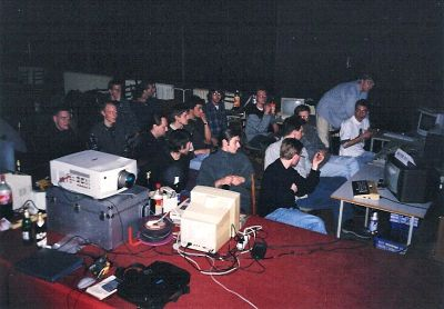 Atari sceners and audience looking at some big-screen show