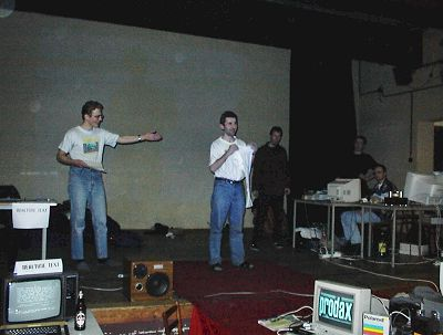 Wotnau - the coferencier on the left. Raster receiving another T-Shirt for his great Atari demo called Self Demo. Speccy organisers in the background. (both from Czech Republic)